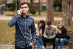 Les jeunes profitant d'un agréable moment en parc Séance masculine et femelle au banc et aux téléphones d'utilisation Images stock
