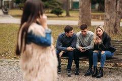 Les jeunes profitant d'un agréable moment en parc Séance masculine et femelle au banc et aux téléphones d'utilisation Image libre de droits
