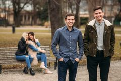 Les jeunes profitant d'un agréable moment en parc Séance masculine et femelle au banc et aux téléphones d'utilisation Images libres de droits