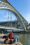 Les jeunes randonneurs non identifiés se reposent sous les DOM célèbres Luis de Ponte de pont à Porto, Portugal photo stock