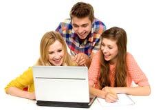 Les jeunes regardant l'ordinateur portatif Image libre de droits