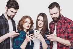 Les jeunes regardant leurs téléphones Images libres de droits