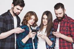 Les jeunes regardant leurs téléphones Image libre de droits