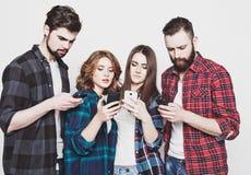 Les jeunes regardant leurs téléphones Photo libre de droits
