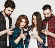Les jeunes regardant leurs téléphones Photos libres de droits