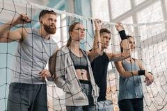 Les jeunes regardant par le filet de volleyball dans la salle de gymnastique Images stock