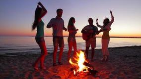 Les jeunes rencontrent l'aube près du feu de camp banque de vidéos