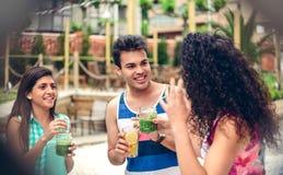 Les jeunes riant et buvant en partie d'été Photos libres de droits