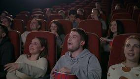 Les jeunes rient du film de comédie dans le théâtre de cinéma Les gens riant du cinéma banque de vidéos