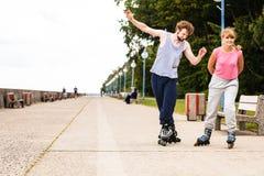 Les jeunes rollblading en passant ensemble Photographie stock libre de droits