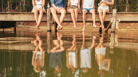 Les jeunes s'asseyant au bord d'un pilier Images stock