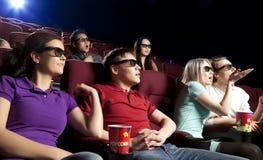 Les jeunes s'asseyant au cinéma, observant un film Photographie stock