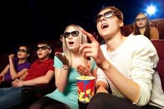 Les jeunes s'asseyant au cinéma, observant un film Photo libre de droits