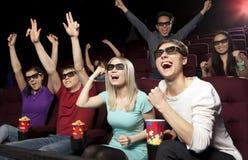 Les jeunes s'asseyant au cinéma, observant un film Image libre de droits