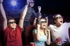 Les jeunes s'asseyant au cinéma, observant un film Photographie stock libre de droits