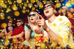 Les jeunes s'asseyant au cinéma, observant un film Images stock