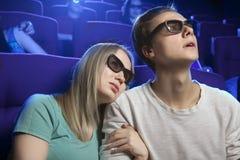 Les jeunes s'asseyant au cinéma, observant un film et mangeant p Photographie stock