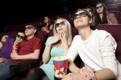 Les jeunes s'asseyant au cinéma, observant un film et mangeant p Image stock