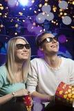 Les jeunes s'asseyant au cinéma, observant un film et mangeant p Photos stock