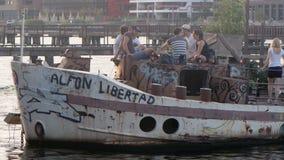 Les jeunes s'asseyant ensemble sur un bateau abandonné banque de vidéos