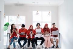 Les jeunes s'asseyant ensemble utilisant leur propre instrument photos stock