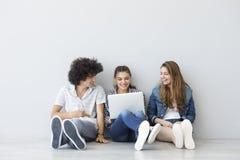 Les jeunes s'asseyant et parlant avec un ordinateur Images stock