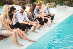 Les jeunes s'asseyant par la piscine Photo stock