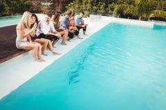 Les jeunes s'asseyant par la piscine Photographie stock libre de droits