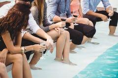 Les jeunes s'asseyant par la piscine Photos libres de droits