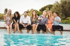 Les jeunes s'asseyant par la piscine Images libres de droits