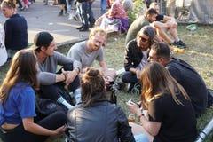 Les jeunes s'asseyant sur l'herbe image libre de droits