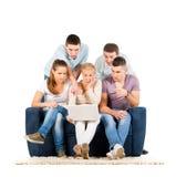 Les jeunes s'asseyant sur un sofa avec la tablette Images stock