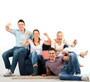 Les jeunes s'asseyant sur un sofa et encourager Photos libres de droits