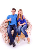 Les jeunes s'asseyant sur un sofa et une soude potable Photo libre de droits
