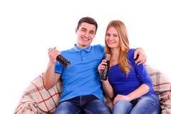Les jeunes s'asseyant sur un sofa et une soude potable i Image stock