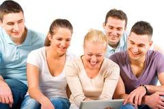 Les jeunes s'asseyant sur un sofa, regardant une tablette Image stock