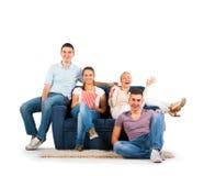 Les jeunes s'asseyant sur un sourire de sofa Image libre de droits
