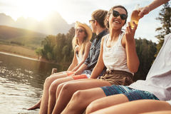 Les jeunes s'asseyant sur une jetée un jour ensoleillé Photographie stock