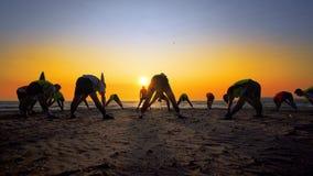 Les jeunes s'exerçant sur la plage vide au coucher du soleil Images stock