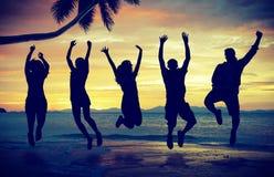 Les jeunes sautant avec l'excitation sur la plage photo libre de droits