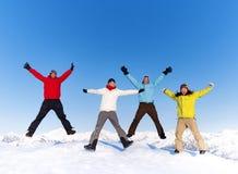 Les jeunes sautant dans la neige et appréciant l'hiver photos libres de droits