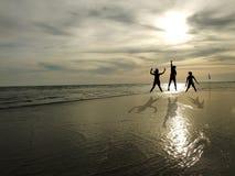 Les jeunes sautant sur la plage avec le fond de coucher du soleil Images libres de droits