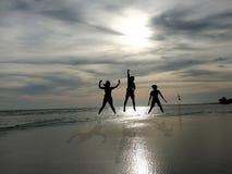 Les jeunes sautant sur la plage avec le fond de coucher du soleil Photo stock