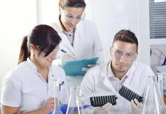 Les jeunes scientifiques attirants d'étudiants de doctorat observant la couleur décalent après le destillation de solution dans l photo libre de droits