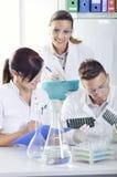 Les jeunes scientifiques attirants d'étudiants de doctorat observant la couleur décalent après le destillation de solution dans l images stock