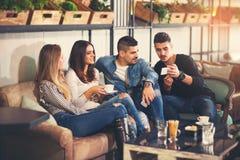 Les jeunes se réunissant dans un café Image libre de droits