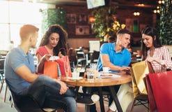 Les jeunes se réunissant dans un café après l'achat Images stock