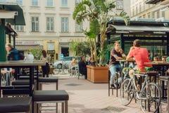 Les jeunes se réunissant et buvant dans la barre extérieure populaire de ville avec les tables grandes Photo libre de droits