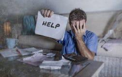 Les jeunes se sont inquiétés chez l'homme d'effort à la maison calculant des dépenses d'impôts de mois avec des paiements de comp images libres de droits