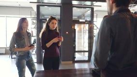Les jeunes se tiennent dans la ligne achetant le café à emporter et payant avec le téléphone portable en café pendant le matin ré banque de vidéos